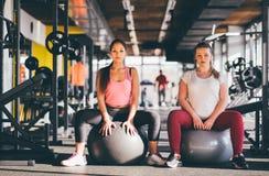 Zwei gesunde junge Mädchen mit den Ball- oder Turnhallenbällen Pilates, die eine Pause von ihrem Training in der Turnhalle machen Lizenzfreie Stockbilder