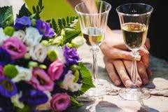 Zwei Gglasses mit Champagne, Paar-Hände, Blumenstrauß lizenzfreies stockbild