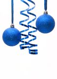Zwei glänzende blaue Weihnachtskugeln mit einem Farbband Stockfotografie