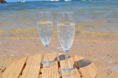 Zwei Gläser Champagne On The Beach With-Seebac Stockbilder