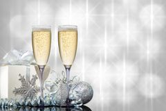 Zwei Gläser Champagner mit einem Geschenk und Weihnachtsspielwaren auf einem schönen Hintergrund stockbild