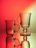 Zwei Gläser in der Hintergrundbeleuchtung Stockfotos