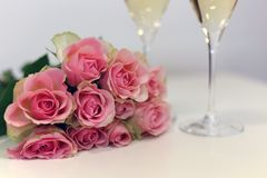 Zwei Gläser des Champagners und des Blumenstraußes, der von schönem hellrotem/gemacht wird, erröten rosa Rosen lizenzfreie stockfotos