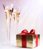 Zwei Gläser des Champagners und des Geschenks stockfotografie