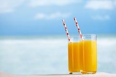 Zwei Gläser des Orangensaftcocktails auf weißem sandigem Strand Lizenzfreie Stockfotos