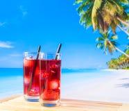Zwei Gläser des roten Cocktails mit Unschärfestrand und -palme Stockfotografie