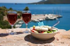 Zwei Gläser des Rotweins und der Schüssel griechischen Salats mit griechischer Flagge an durch die Seeansicht, griechisches Feier stockfotografie