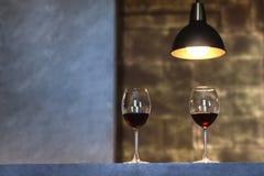 Zwei Gläser des Rotweinstands auf einer Marmortabelle mit einer Lampe, die von oben hängt Horizontales Foto E stockfotos