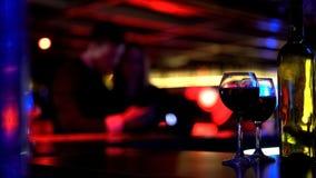 Zwei Gläser des Weins und der Flasche an der Bar im Nachtklub, Paar auf unscharfem Hintergrund lizenzfreies stockfoto