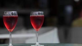Zwei Gläser Dunkelheitshintergrund des rosafarbenen Weins stock video footage