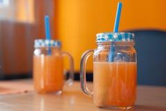 Zwei Gläser frischer Zitrusfruchtsaft mit netten Deckeln und Strohen Stockfotografie