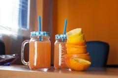 Zwei Gläser frischer Zitrusfruchtsaft mit netten Deckeln und Strohen zusammen mit einem Stapel von zusammengedrückten Zitrusfrüch Lizenzfreies Stockbild