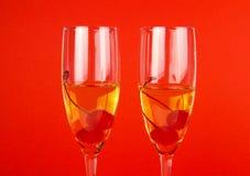 Zwei Gläser mit Champagner und Kirschen auf Rot Lizenzfreies Stockfoto
