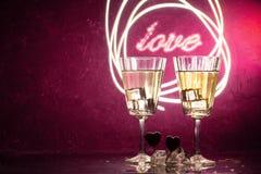 Zwei Gläser mit einem Cocktail und zwei Herzen, Valentinstagkonzept stockfotos