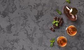 Zwei Gläser mit Kognak, Whiskysteinen und Schokolade stockfotografie