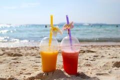 Zwei Gläser mit Mangosaft und Wassermelonensaft auf dem Strand im sonnigen Sommer verwittern Stockfoto