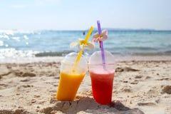 Zwei Gläser mit Mangosaft und Wassermelonensaft auf dem Strand im sonnigen Sommer verwittern Lizenzfreies Stockbild