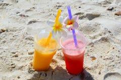 Zwei Gläser mit Mangosaft und Wassermelonensaft auf dem Strand im sonnigen Sommer verwittern Stockbilder