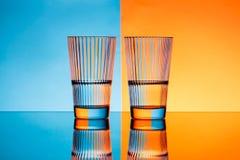 Zwei Gläser mit Wasser über blauem und orange Hintergrund Stockbilder