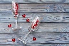Zwei Gläser, rote Zahlen in Form eines Herzens auf einem hölzernen Hintergrund Romantisches Datum Stockfotografie