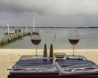 Zwei Gläser Rotwein auf einem Strandseitenrestaurant lizenzfreie stockfotos