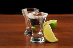 Zwei Gläser Tequila, Salz und Kalk Stockfotografie