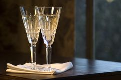 Zwei Gläser Waterford-Champagne auf hölzerner Tabelle Stockfotografie