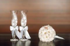 Zwei Gläser weiße Gänseblümchen des Champagners und eines Hochzeitsblumenstraußes stockfoto