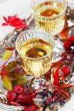 Zwei Gläser Weißwein auf einem Weinlesesilbertablett verziert mit Herbsttraube, Blättern und Himbeeren, romantisches Picknick Stockbilder