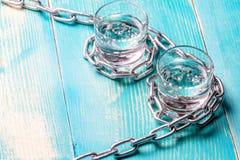 Zwei Gläser Wodka auf einer hölzernen gemalten Tabelle werden durch eine Kette des Metalls angeschlossen Lizenzfreies Stockfoto