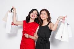 Zwei glückliche attraktive junge Frauen mit Einkaufstaschen auf weißem BAC Lizenzfreie Stockfotografie