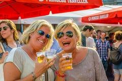 Zwei glückliche blonde Frauen mit einem Glas Bier Lizenzfreie Stockbilder