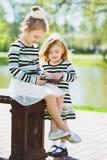 Zwei glückliche blonde kleine Mädchen oder Schwestern, die Tablette betrachten Stockbild