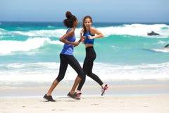 Zwei glückliche Frauen, die auf dem Strand laufen Lizenzfreies Stockbild