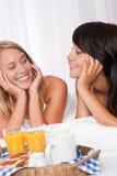 Zwei glückliche Frauen, die frühstücken Stockfoto
