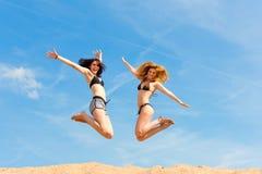 Zwei glückliche Frauen, die hoch mit Spaß springen Lizenzfreies Stockfoto