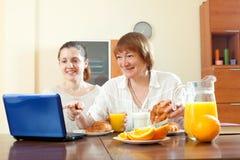 Zwei glückliche Frauen, die Laptop während des Frühstücks verwenden Stockfoto