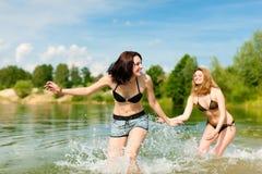 Zwei glückliche Frauen, die Spaß in See im Sommer haben Lizenzfreie Stockfotografie
