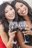 Zwei glückliche Frauen-Freunde, die zusammen Wein trinken Stockbild