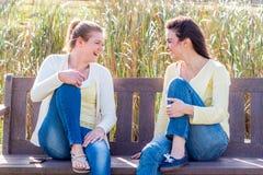 Zwei glückliche Freunde, die auf der sprechenden und aufeinander einwirkenden Parkbank sitzen stockbild
