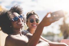 Zwei glückliche Freunde, die Foto durch Mobile sich machen Stockbilder