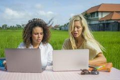 Zwei glückliche Freundinnen, die draußen am schönen Internet-Café mit Laptop-Computer kaukasischer Frau und einem Afromischmädche Stockfotografie