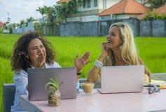Zwei glückliche Freundinnen, die draußen am schönen Internet-Café mit Laptop-Computer kaukasischer Frau und einem Afromischmädche Lizenzfreie Stockfotos