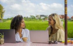 Zwei glückliche Freundinnen, die draußen am schönen Internet-Café mit Laptop-Computer kaukasischer Frau und einem Afromischmädche Stockfotos