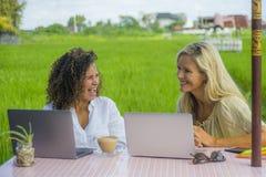 Zwei glückliche Freundinnen, die draußen am schönen Internet-Café mit Laptop-Computer kaukasischer Frau und einem Afromischmädche Lizenzfreies Stockfoto
