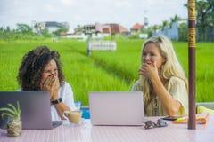 Zwei glückliche Freundinnen, die draußen am schönen Internet-Café mit Laptop-Computer kaukasischer Frau und einem Afromischmädche Lizenzfreies Stockbild