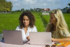 Zwei glückliche Freundinnen, die draußen am schönen Internet-Café mit Laptop-Computer kaukasischer Frau und einem Afromischmädche Stockbilder