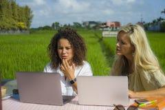 Zwei glückliche Freundinnen, die draußen am schönen Internet-Café mit Laptop-Computer kaukasischer Frau und einem Afromischmädche Stockfoto