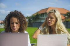 Zwei glückliche Freundinnen, die draußen am schönen Internet-Café mit Laptop-Computer kaukasischer Frau und einem Afromischmädche Stockbild