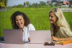 Zwei glückliche Freundinnen, die draußen am schönen Internet-Café mit Laptop-Computer kaukasischer Frau und einem Afromischmädche Lizenzfreie Stockfotografie
